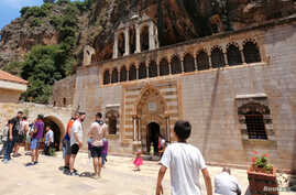 FILE - People visit the Monastery of Saint Anthony of Qozhaya in the heart of the Qadisha valley, in Zgharta district, Lebanon, June 23, 2019.