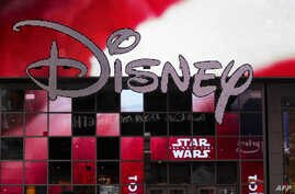 FILE - The Disney logo is displayed outside the Disney Store in Times Square in New York City, Dec. 14, 2017.