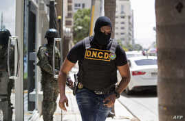 An agent of the Dominican National Drug Control Board (DNCD) and a soldier take part in the dismantling operation of a drug trafficking network, in Santo Domingo, Aug. 20, 2019.