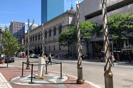 Light spires and one of the stone pillars stand along Boylston Street after installation was finished, Aug. 19, 2019, in Boston to memorialize the Boston Marathon bombing victims at the sites where they were killed.