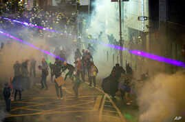 Protesters react from tear gas fired by riot policemen during the anti-extradition bill protest at Causeway Bay in Hong Kong, Aug. 4, 2019.