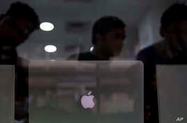 FILE - Indian customers check an apple laptop at a store in New Delhi, May 17, 2016.