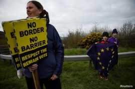 A woman carries signs as children hold an EU flag as they attend a protest against Brexit on the border crossing between the Republic of Ireland and Northern Ireland in Carrickcarnon, Ireland, March 30, 2019.