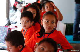 Migrant children take English lessons at a bus converted in a classroom as part of Schools On Wheels program by California's 'Yes We Can' organization, in Tijuana, Mexico, Aug. 2, 2019.