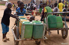 Displaced children that fled from their villages in northern Burkina Faso, following attacks by assailants, push carts loaded with water containers at a school on the outskirts of Ouagadougou, June 15, 2019.
