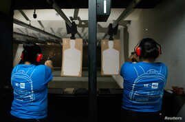 Nicole Navarro (L) and Adriana Retana, who said they wanted to improve their marksmanship after a gunman killed 22 people at a local Walmart, practice shooting at a gun range in El Paso, Texas, Aug. 12, 2019.