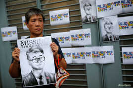 A woman holds a poster of Simon Cheng, a staff member at the British consulate, during a protest outside the British Consulate-general office in Hong Kong, Aug. 21, 2019.