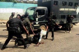 Police officers pull a journalist during an anti-government protest in Lagos, Nigeria.