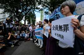 Activists hold placards during a rally in front of the Tokyo District Court in Tokyo, Sept. 19, 2019, after the court acquitted three former officials from the firm that operated the Fukushima nuclear plant.