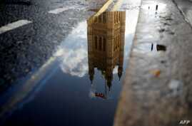 The Houses of Parliament are reflected in a puddle of rainwater in central London, Sept. 24, 2019.