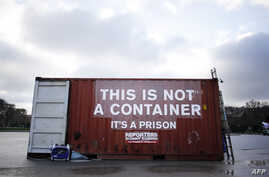 """FILE - A shipping container bearing the slogan """"This is not a container, it is is prison"""" stands in position during a demonstration by Reporters Without Borders in support of imprisoned journalists, including those from Eritrea, in Paris, Dec. 16, 2014."""
