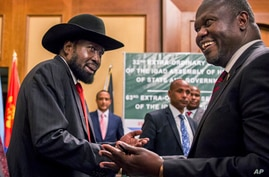 FILE - South Sudan's President Salva Kiir, left, and opposition leader Riek Machar, right, shake hands during peace talks in Addis Ababa, Ethiopia, June 21, 2018.