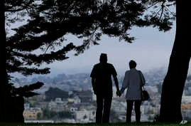 In this July 3, 2017 file photo, a man and woman walk under trees down a path at Alta Plaza Park in San Francisco.