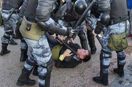 FILE - Police officers detain a person during an unsanctioned rally in Moscow, July 27, 2019.
