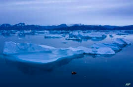 FILE - A boat navigates next to large icebergs near the town of Kulusuk, in eastern Greenland, Aug. 15, 2019.