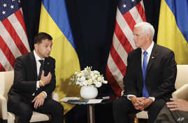 Ukraine's President Volodymyr Zelenskiy, left, gestures next to U.S. Vice President Mike Pence, during a bilateral meeting in Warsaw, Poland, Sunday, Sept. 1, 2019.