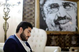 FILE - Abdullah Morsi, the youngest son of Egypt's former President Mohamed Morsi, sits in front of a framed image of his father that was printed on a flag during the 2013 Rabaah al-Adawiya sit-in, at his home in Cairo, Egypt.