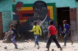 Children play soccer next to a defaced portrait of former Zimbabwean President Robert Mugabe in Harare, Sept, 6 2019.