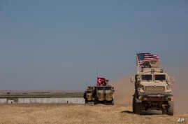 "FILE - Turkish and American forces conduct their first joint ground patrol in the so-called ""safe zone"" on the Syrian side of the border with Turkey, seen in the background, near Tal Abyad, Syria, Sept. 8, 2019."
