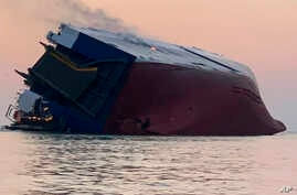Coast Guard crews and port partners respond to an overturned cargo vessel with a fire on board Sunday, Sept. 8, 2019, in St. Simons Sound, Ga.