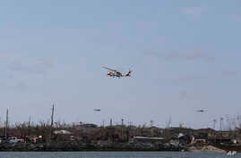 US Coast Guards helicopters fly over Marsh Harbor after it was devastated by Hurricane Dorian on Abaco Island, Bahamas, Sept. 8, 2019.