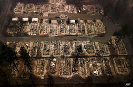 FILE - An aerial file photo shows the remains of residences leveled by the Camp wildfire in Paradise, Calif., Nov. 15, 2018.