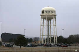 FILE - Vehicles park around a water tower at Fort Riley, Kansas, Feb. 9 2015. According to a criminal complaint filed Monday, a U.S. Army soldier has been arrested after sharing bomb-making instructions online.