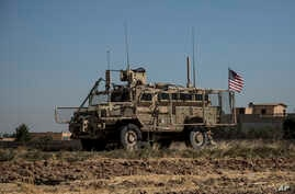"An American armored vehicle patrols with Turkish forces, as they conduct their second joint ground patrol in the ""safe zone"" on the Syrian side of the border with Turkey, in Rahaf village, near the town of Tal Abyad, northeastern Syria, Sept. 24, 2019."