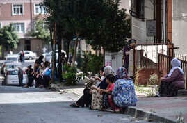 People sit and stand on the streets after evacuating their homes, following an earthquake in Istanbul, Sept. 26, 2019.