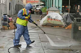 In this Feb. 26, 2016 file photo, a city worker uses a power washer to clean the sidewalk by a tent city along Division Street in San Francisco.