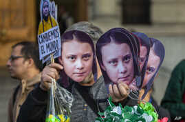 A man sells Greta Thunberg masks during a climate protest rally in Santiago, Chile, Sept. 27, 2019.