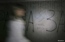 "A woman walks past a swastika and the inscription ""Death to Jews' painted on a wall in an underpass in Kyiv, Ukraine, May 29, 20"