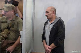Volodymyr Tsemakh, suspected of involvement in the downing of the Malaysia Airlines Flight MH17 plane in 2014, stands inside a defendants' cage during a court hearing in Kyiv, Ukraine, Sept. 5, 2019.