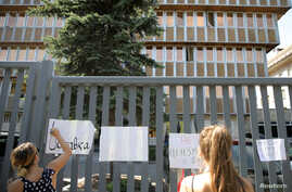 """A protester writes """"Resignation"""" on a banner during a demonstration outside Bulgaria's national radio building in Sofia, Bulgaria, Sept. 13, 2019."""