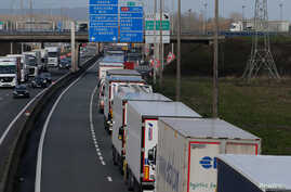 FILE - Trucks queue on the motorway as French Customs Officers increase controls on transported goods to protest the lack of resources as the Brexit date approaches, in Calais, France, March 13, 2019.