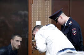 Defendant Pavel Ustinov, accused of using violence against an officer of Russia's National Guard during an unauthorized rally to demand free elections, listens to a lawyer during a court hearing in Moscow, Russia September 16, 2019.