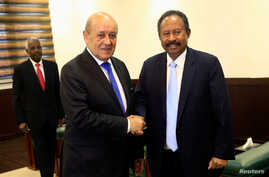 Sudan's prime minister Abdalla Hamdok shakes hands with French Foreign Minister Jean-Yves Le Drian during their meeting in Khartoum, Sudan, Sept. 16, 2019.