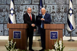 Israeli President Reuven Rivlin gives Israeli Prime Minister Benjamin Netanyahu a file during a nomination ceremony at the President's residence in Jerusalem, Sept. 25, 2019.