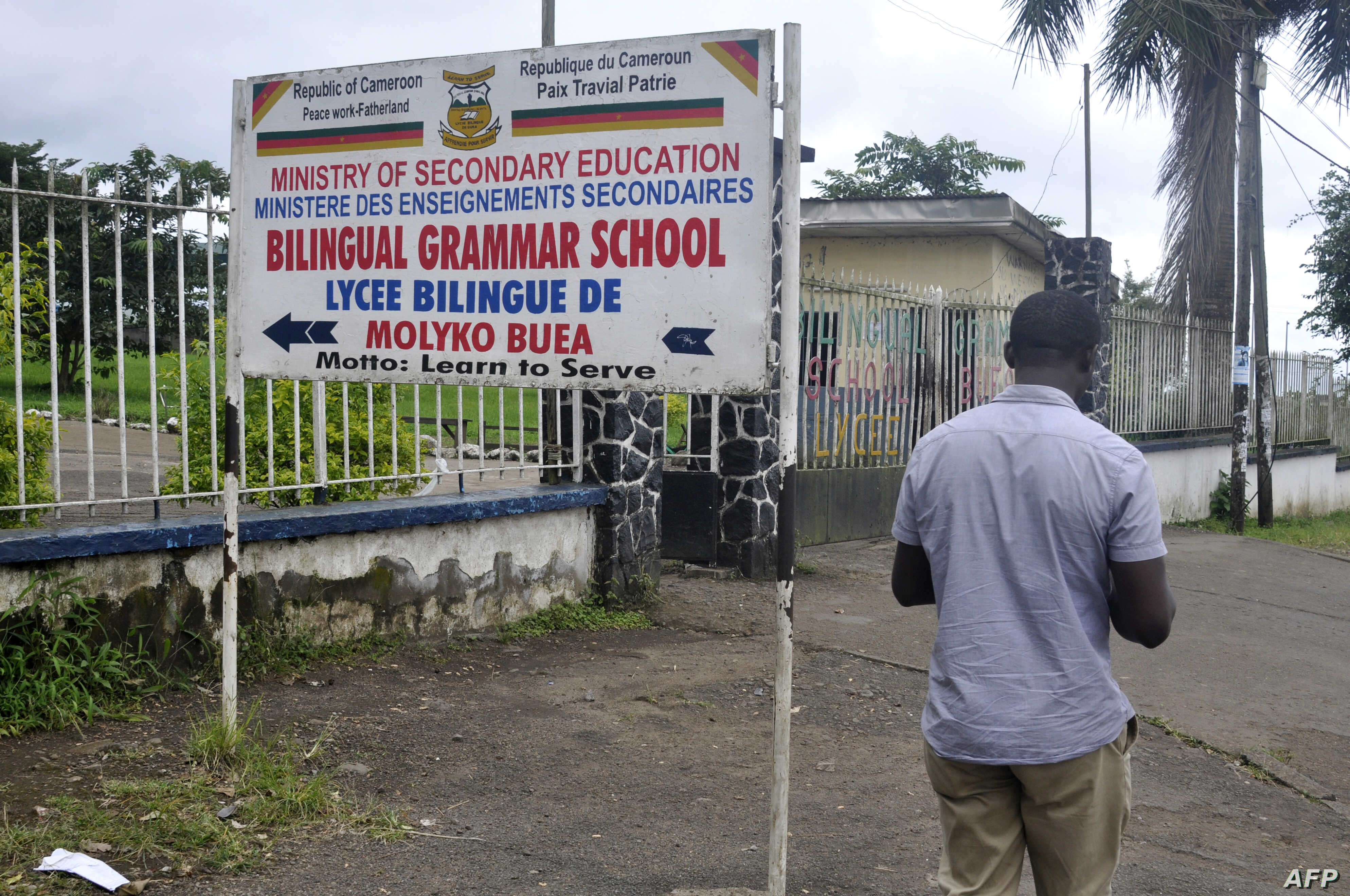 FILE - A man walks past the entrance of the bilingual Lycee of Buea, capital of south west Cameroon, one of the two regions of the country in the grip of a violent crisis on Sept. 24, 2019.