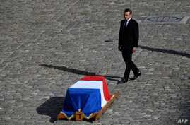 French President Emmanuel Macron stands in front of the coffin of former French president Jacques Chirac during a military tribute at the Invalides (Hotel des Invalides) in Paris, Sept. 30, 2019.
