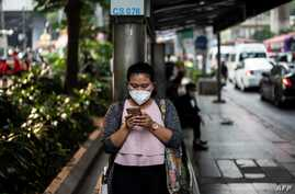 FILE - A woman, wearing a face mask, uses her mobile phone while waiting at a bus stop in Bangkok, Thailand, Jan. 30, 2019.