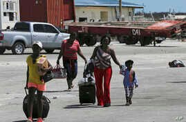 Evacuees carry their belongings as they walk to a ferry to depart for Nassau in the aftermath of Hurricane Dorian, at the port of Marsh Harbor, Abaco Island, Bahamas, Sept. 8, 2019.