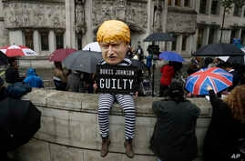 A person dressed as a caricature of British Prime Minister Boris Johnson in a prison uniform sits outside the Supreme Court in London, Sept. 24, 2019, after it made it's decision on the legality of Johnson's five-week suspension of Parliament.
