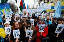 FILE - Ukrainian and Crimean Tatar activists hold portraits with the names of victims of the Russian annexation of Crimea, during a rally in Kyiv, Ukraine, Feb. 26, 2017.