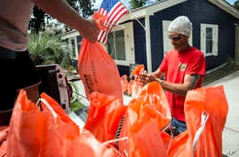 Tom Sikes, right, helps his friend Joey Spalding, left, fill sandbags at Spalding's home in Tybee Island, Ga., Sept. 3, 2019, be