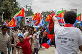 Eritrean refugees and dissidents, some holding Eritrean flags and some dressed as Eritrean military members to illustrate beatings and torture, left, demonstrate against repressions in their home country in Addis Ababa, Ethiopia, June 23, 2016.