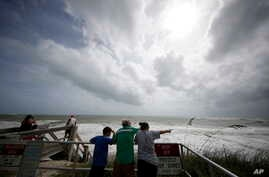 People on a boardwalk look out over the high surf from the Atlantic Ocean, in advance of the potential arrival of Hurricane Dorian, in Vero Beach, Florida, Sept. 2, 2019.