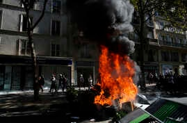 People walk past a burning barricade during a climate demonstration, in Paris, Saturday, Sept. 21, 2019. Scuffles broke out in Paris between some violent activists and police which responded with tear gas at a march for climate gathering thousands of people in Paris.