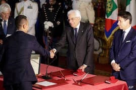 Foreign Minister Luigi Di Maio, left, shakes hands with Italian President Sergio Mattarella, center, as Prime Minister Giuseppe Conte looks on, during a swearing-in ceremony at the Quirinale Presidential Palace, in Rome, Italy, Sept. 5, 2019.