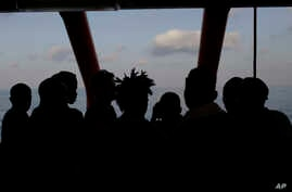 Rescued migrants are silhouetted as they look out at the horizon aboard the Ocean Viking, in the Mediterranean Sea, Sept. 13, 2019.